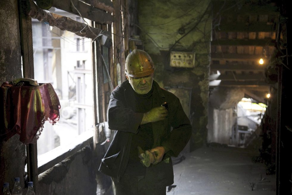 Georgia. Chiatura City. Mineworker scratches out a cross on his helmet.